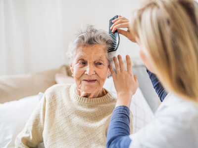 An unrecognizable health visitor combing hair of senior woman sitting on a sofa at home.