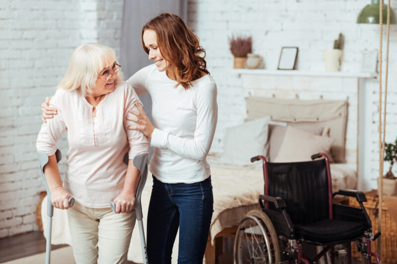 I will help you. Positive aged disabled woman waling with crutches while her caring smiling granddaughter helping her at home