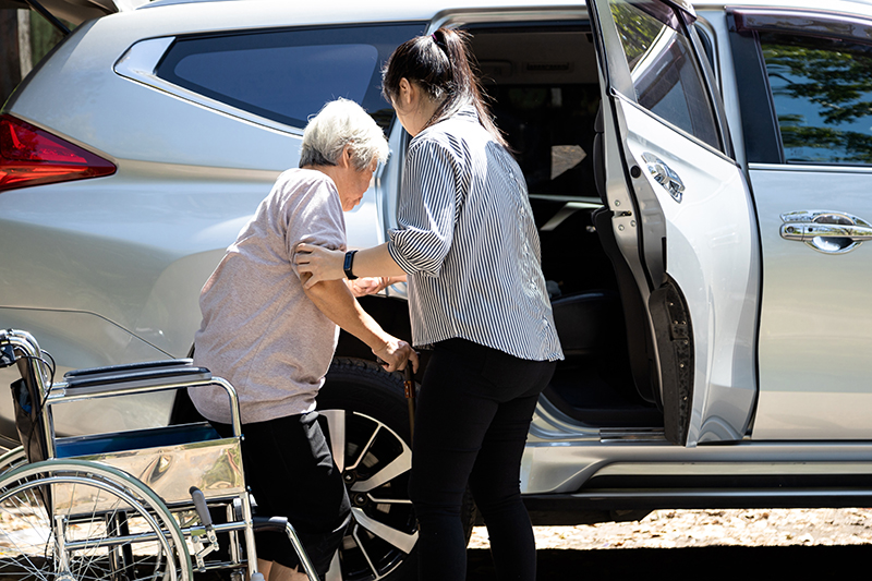 Asian female caregiver helping disabled elderly woman in wheelchair to get into the car,helpful daughter care and support senior mother to stand up from wheelchair in outdoor, caring for old people