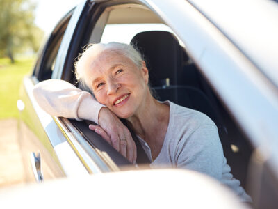 road trip, travel and old people concept - happy senior woman driving in car with open window