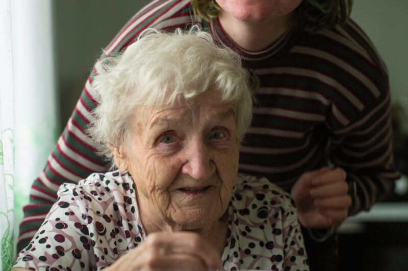 Portrait of old woman with her granddaughter in the kitchen at home.