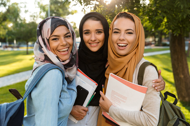 Image of a happy young arabian women students holding books in park outdoors.
